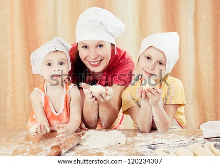 Mother with two daughters, all of the flour with the dough.