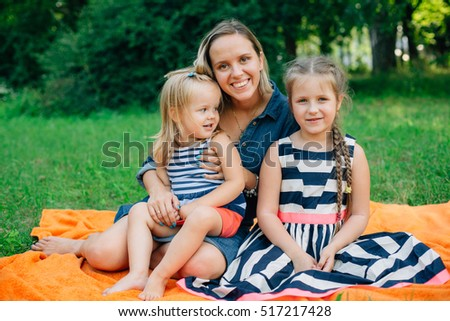 Mother with two daughters in striped clothing sitting on orange blanket in park. Happy parenting concept
