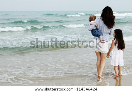Mother with two daughters on the beach - stock photo