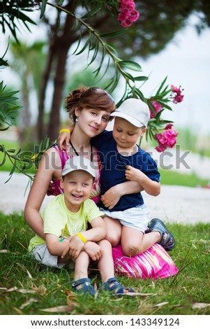 Mother with two her children in the park - stock photo