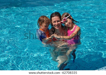 Mother with two kids having fun in swimming pool - stock photo