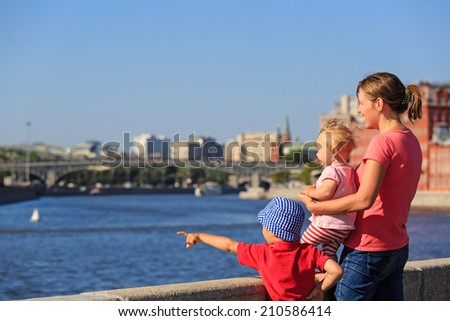 mother with two kids looking at summer city