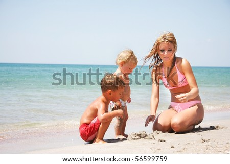 mother with two kids on beach - stock photo