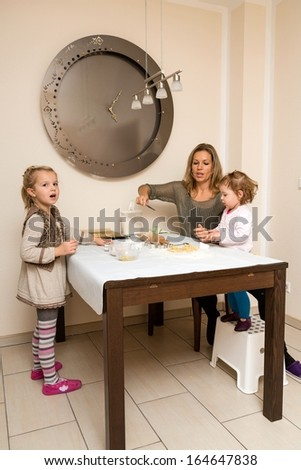Mother with two little children make cookies. Advent, X-mas - stock photo