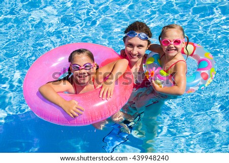 mother with two little girls playing  in water - stock photo
