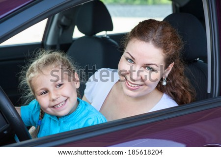 Mother with young daughter sitting together on the driver seat in car - stock photo