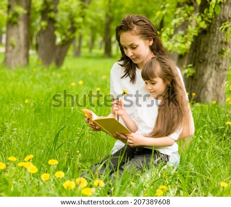 mother with young girl reading book in park - stock photo