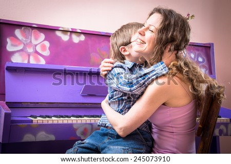 Mother with young son to play the piano - stock photo