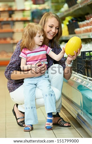 Mother woman and little girl choosing melon during family shopping at fruit vegetable supermarket store - stock photo