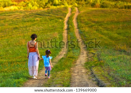 mother woman little girl my daughter go on rural road through green field in summer - stock photo