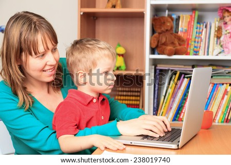 mother working on laptop from home with little son - stock photo
