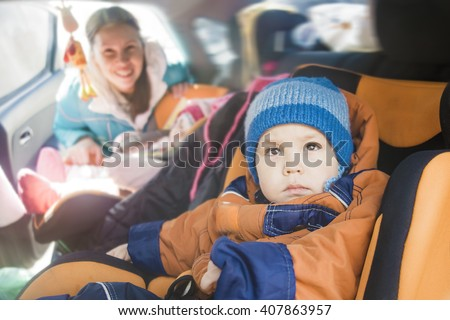 Mother worried about her children's safety in a car Son and daughter near to mom Babes sitting inside modern auto People look at camera The idea of safe traffic