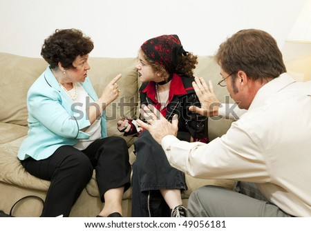 Mother yelling at her teen daughter during a family counseling session.