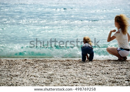 Mother young woman and son baby boy sit on pebble beach near blue sea windy weather on natural background, copy space