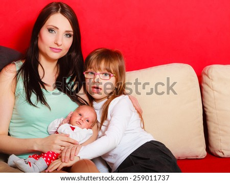 Motherhood and happiness concept. Portrait woman with her children little daughter preschooler and newborn baby girl child on couch at home