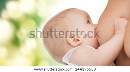 motherhood, children, people and care concept - close up of mother breast feeding adorable baby over green background - stock photo