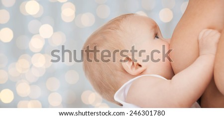 motherhood, children, people and care concept - close up of mother breast feeding adorable baby over holidays lights background - stock photo