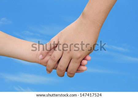 motherhood concept with a woman holding a child's hand outdoors on a warm day