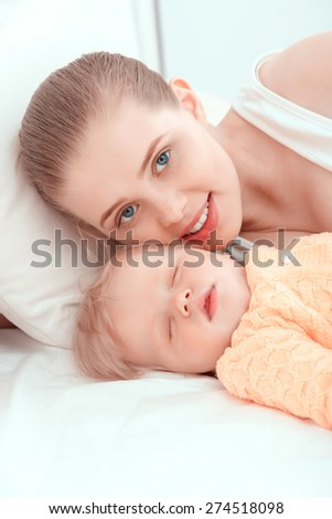 Motherhood. Mother looking at the camera lying near her sleeping baby  - stock photo
