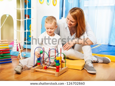 Mothers and her little blond boy learning to solve puzzle with toys - stock photo