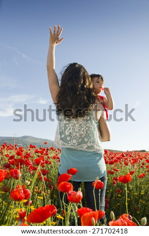 mothers back lifting baby at sunset with hand up - stock photo