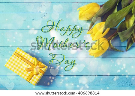 Mothers day background with yellow tulips and gift box on blue painted wooden background. Happy mother's day concept. Mothers Day message. - stock photo