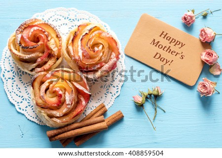 Mothers day card. Homemade Apple rose cake with sugar powder on blue  wooden background. Top view.  Handmade gift for mom/ Mothers day concept card. - stock photo