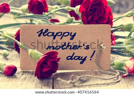 Mothers day card with carnations on wooden board. Vintage filter. - stock photo