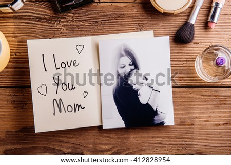 Mothers day composition. Black-and-white picture of mother holding her little baby, greeting card with I love you Mom text and various cosmetics. Studio shot on wooden background. - stock photo