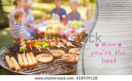 Mothers day greeting against happy family eating barbecue - stock photo