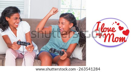 mothers day greeting against happy mother and daughter playing video games together on sofa - stock photo