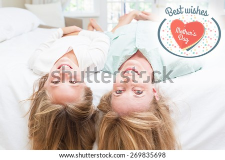 mothers day greeting against mother and daughter looking at camera lying on the bed - stock photo