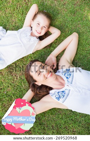mothers day greeting against mother and daughter lying on grass - stock photo