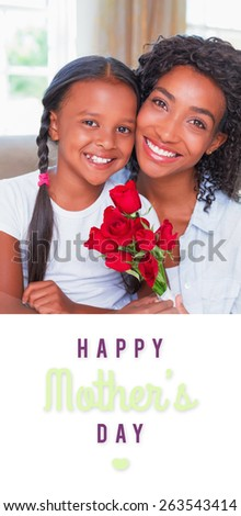 mothers day greeting against pretty mother sitting on the couch with her daughter holding roses - stock photo