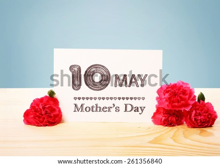 Mothers Day May 10th Card with Carnation Flowers on Top of a Wooden Table  - stock photo