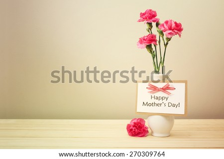 Mothers day message with pink carnations in a white vase - stock photo