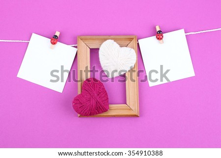 Mothers day, Valentine day empty card with felt hearts hanging with clothespins over pink board. Copy space for text on white paper. - stock photo