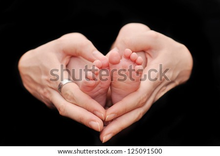 Mothers hands holding newborn baby feet, isolated on black