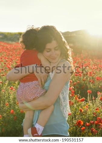 Mothers hug baby in sun light