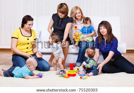 Mothers in the living room look at their babies playing - stock photo