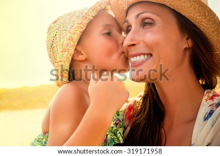 mothers love daughter kissing on sunny day - stock photo