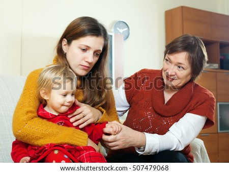 Mothers problems. Mature woman comforting adult daughter with baby in living room at home