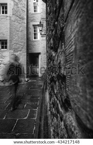 Motion blur as a man walks through one of the many narrow closes (lane) off the Royal Mile in Edinburgh, Scotland