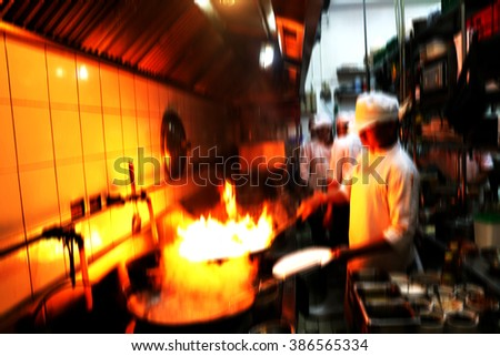 Motion blur chefs a restaurant kitchen cooking.