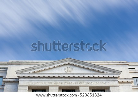 Motion blur clouds illustrating time moving quickly past  front of Dirksen Senate office building Washington DC showing gridlock at Congress or long delays in getting legislation passed in Government
