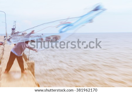 motion blur fisherman casting his net from the boat at Hua Hin fishing pier. - stock photo