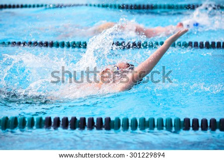 Motion blur image of a boy swimming backstroke in a race.  - stock photo