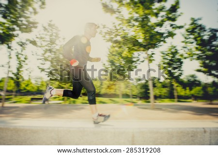 motion blur image of young man running practicing sport in city park with extreme backlight lens flare lighting effect in fitness and healthy lifestyle concept