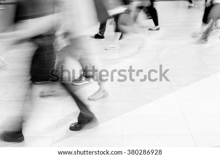 Motion blur legs of people walking on pathway - black and white filter - stock photo