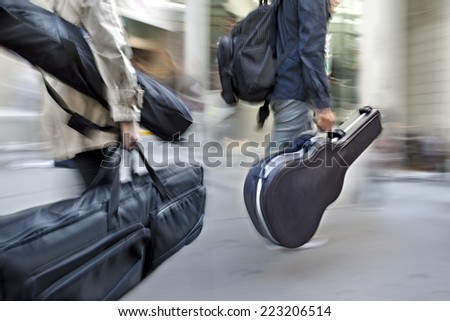 motion blur man on a city street with a musical instrument - stock photo